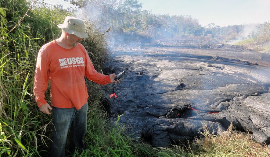 In this Oct. 22, 2014 photo provided by the U.S. Geological Survey, a geologist marks the coordinates of the Kilauea lava flow front with a GPS unit. A 13-mile finger of lava from Kilauea Volcano has started to again move quickly, and could hit a secondary road sometime Friday, Oct. 24, 2014. Officials on Hawaii's Big Island won't start evacuating people until the lava flow is within three to five days of affecting Pahoa residents. (AP Photo/U.S. Geological Survey)