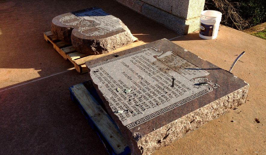 The damaged remains of a Ten Commandments monument are gathered on the Oklahoma State Capitol grounds Friday, Oct. 24, 2014 in Oklahoma City. Authorities say someone drove across the Oklahoma Capitol lawn and knocked over the monument. The American Civil Liberties Union had been suing to have the monument removed, arguing it violates the Oklahoma Constitution. (AP Photo/Sean Murphy)