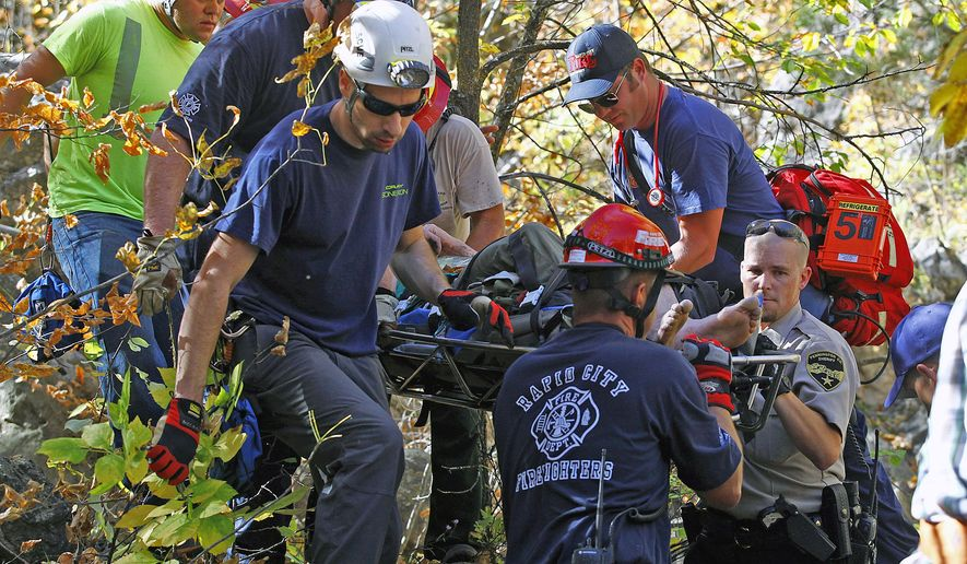 ADVANCE FOR MONDAY OCT. 27 - In this Sept. 26, 2014 photo, emergency personnel work to get a Jimmy Burckhard to Dark Canyon Road outside of Rapid City, S.D. after he fell 70 feet while rock climbing. (AP Photo/Rapid City Journal, Chris Huber) TV OUT