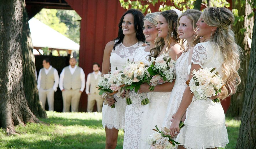 In this Sept. 13, 2014 photo, bride Kimmy Anderson, center, had her bridesmaids wear lace and cowboy boots to go with her country-themed wedding at Willoughby Heritage Farm in Collinsville, Ill., on her wedding day to Nick Nasti. The couple exchanged vows surrounded by tall trees and blue skies. They danced the night away in a big red barn. (AP Photo/Belleville News-Democrat, Maureen Houston)