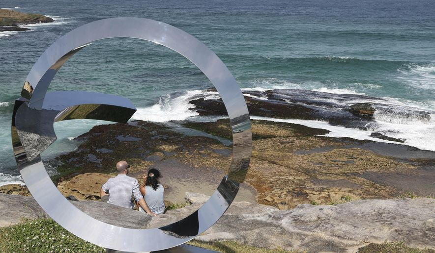 """A couple sit on rocks near a sculpture titled """"Wind Stone - The Threshold of Consciousness"""" created by artist Koichi Ishino at Sculpture By The Sea in Sydney, Australia, Friday, Oct. 24, 2014. Sculptures and other art forms created by 109 artists from 16 countries, are displayed across the costal area of Sydney. (AP Photo/Rob Griffith)"""