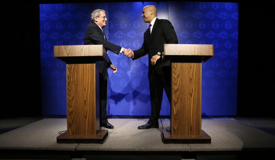 Republican candidate for Senate, Jeff Bell, left, and incumbent Democrat Cory Booker shake hands before their debate Friday, Oct. 24, 2014, in Trenton, N.J. New Jersey's U.S. Senate candidates participated in their first and only debate of the campaign and fielded questions at the League of Women Voters event. (AP Photo/Mel Evans)