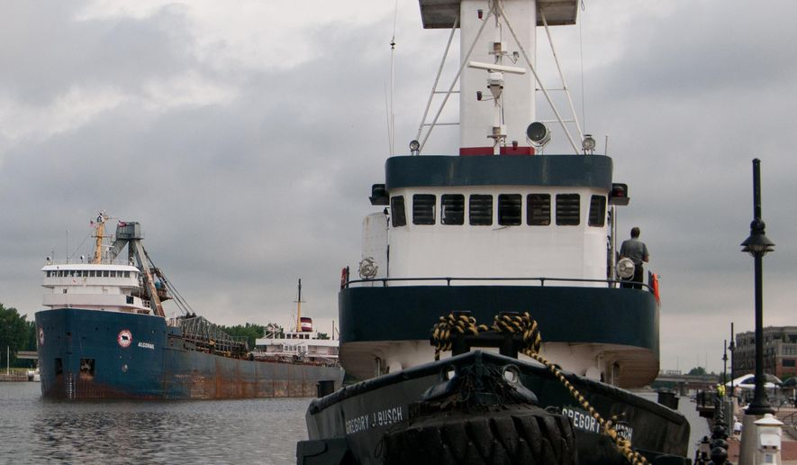 FILE - In this Tuesday, June 25, 2013 file photo, the Gregory J Busch tug boat, right, arrives in Bay City, Mich., to help move the Algorail, left, that was stuck in the Saginaw River in downtown Bay City. Saginaw County has approved a $594,000 river-deepening feasibility study, The Saginaw News reported. (AP Photo/The Bay City Times, Yfat Yossifor, file) LOCAL TV OUT; LOCAL INTERNET OUT