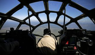 Charles Chauncey, who flew 35 missions in a B-29 bomber during World War II, sits in the gunner position of a B-29 as it flies from Baton Rouge, La., en route to New Orleans, Thursday, Oct. 23, 2014. The bomber will spend the weekend at the WWII AirPower Expo put on by the Commemorative Air Force and the National World War II Museum. (AP Photo/Gerald Herbert)