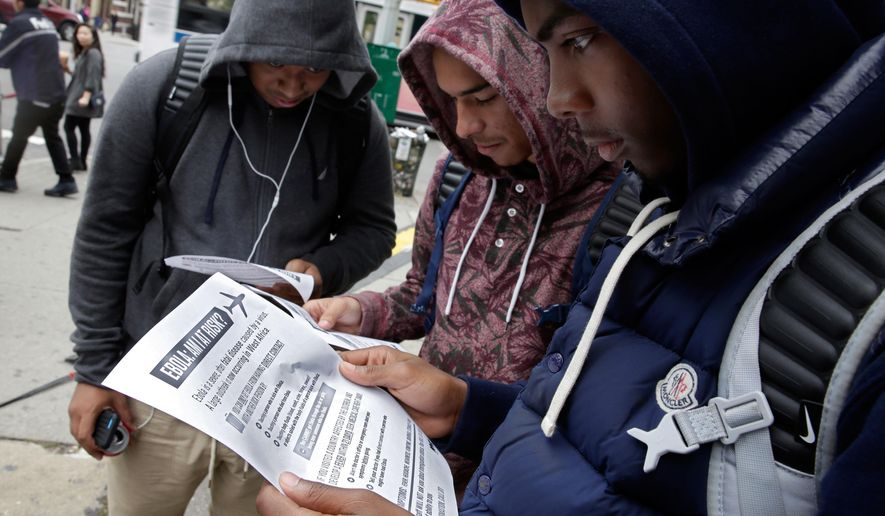 Mott Hall High School student Brian Binion, right, and fellow students read fliers about Ebola risk, near the apartment building of Ebola patient Dr. Craig Spencer, in New York,  Friday, Oct. 24, 2014. Since there's no specific treatment, care is focused on easing symptoms to give the body enough time to fight off an infection, (AP Photo/Richard Drew)