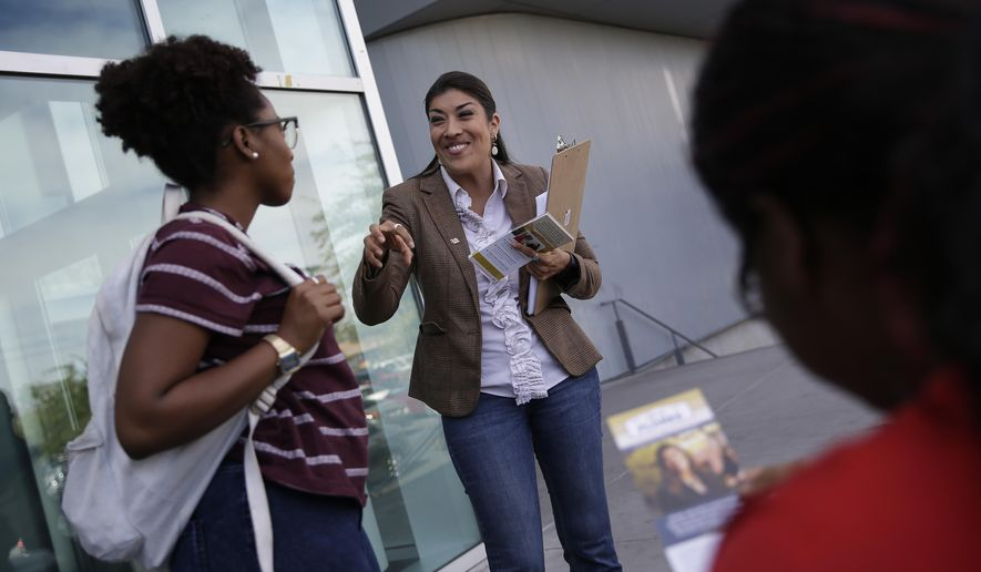 Democratic lieutenant governor candidate Lucy Flores, center, speaks with Kendra McGlothen, left, at the University of Nevada, Las Vegas Thursday, Oct. 23, 2014, in Las Vegas. Flores was on a 24 hour campaign blitz to push more Nevada voters to the polls.(AP Photo/John Locher)
