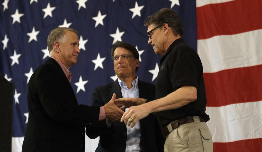 U.S. Senate candidate and Speaker of the North Carolina House Thom Tillis, left, North Carolina Gov. Pat McCrory and Texas Gov. Rick Perry shake hands during a conservative rally in Smithfield, N.C., Friday, Oct. 24, 2014. (AP Photo/Gerry Broome)