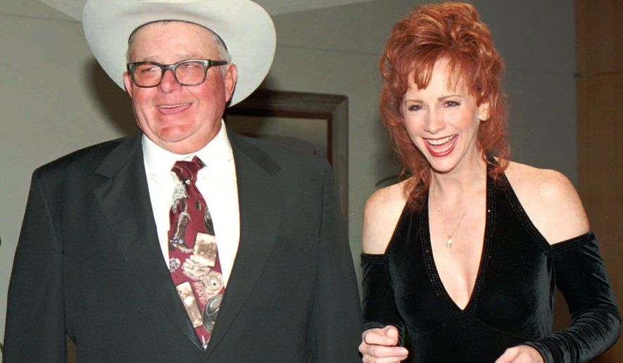 "File-This file photo from 1995 shows Reba McEntire, right,  and her ""daddy"" Clark McEntire having a laugh with members of the media prior to induction ceremony at the National Cowboy Hall of Fame.  A post on the singer's verified Twitter account Friday, Oct. 24, 2014, says Clark McEntire passed away Thursday night in Coalgate, Okla. (AP Photo/The Oklahoman, Jim Beckel, File)"