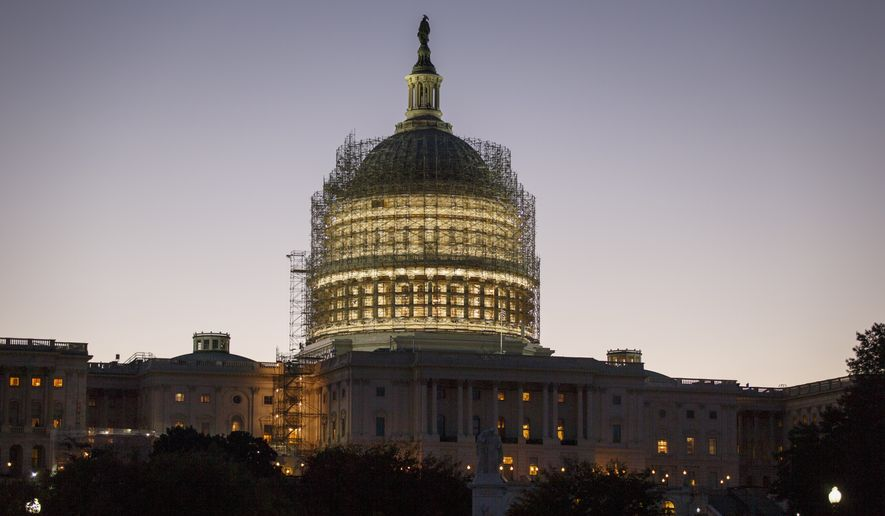 The Capitol Dome is nearly obscured by scaffolding at dawn in Washington, Friday, Oct. 24, 2014, for a long-term repair project to fix cracks, leaks and corrosion in the cast-iron structure. The House and Senate are adjourned until after the midterm election.   (AP Photo/J. Scott Applewhite)