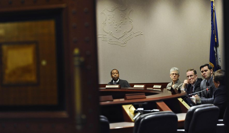 Scott Jackson, Chairman of the Sandy Hook Advisory Commission, center, listens as committee member Dr. Alice M. Forrester, right, speaks, during a meeting of the commission at the Legislative Office Building, Friday, Oct. 24, 2014, in Hartford, Conn.  Victims' parents scheduled to attend the meeting did not show. (AP Photo/Jessica Hill)