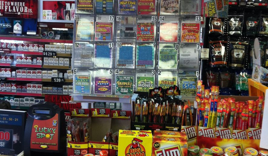 FILE - In this Thursday, Aug. 16, 2012 file photo, lottery scratch-off tickets and other items for sale are displayed at a Sunoco gas station and market in Lapeer, Mich. More than 7,200 people who won at least $1,000 in the Michigan Lottery last year were living in households that received public assistance, according to a state report. (AP Photo/Mike Householder, file)