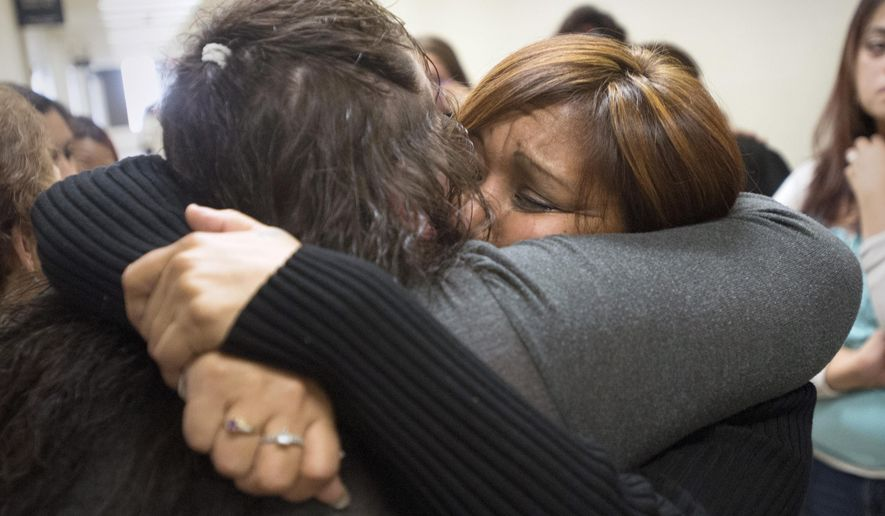 Theresa Medel, right, the mother of Angelica Olivarez, hugs one of many family members outside the courtroom,Friday, Oct. 24, 2014 in Saginaw, Mich. The jury convicted Michael D. Lawrence, 25, of felony murder and two other felonies in the April 15, 2013, homicide of Olivarez, the mother of his child, inside Olivarez's home at 1622 N. Bond on Saginaw's West Side. (AP Photo/The Saginaw News, Jeff Schrier) ALL LOCAL TELEVISION OUT; LOCAL TELEVISION INTERNET OUT