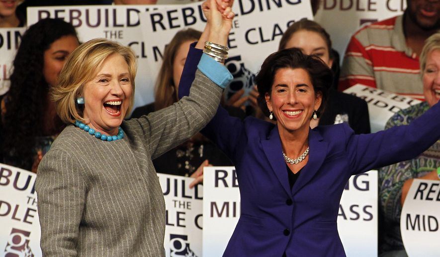 Hillary Rodham Clinton, left, holds up the hand of  Democratic gubernatorial nominee Gina Raimondo, right, while campaigning for her at Rhode Island College in Providence, R.I., Friday Oct. 24, 2014. (AP Photo/Stew Milne)