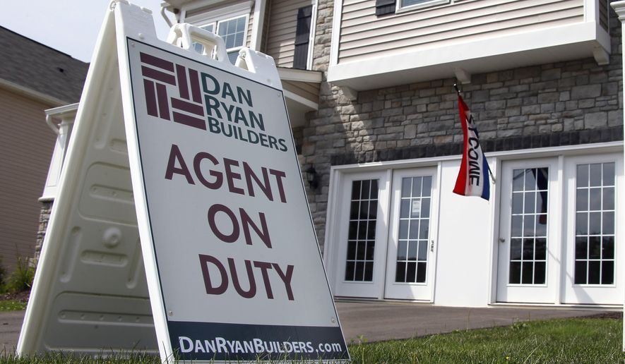In this photo made on Wednesday, Sept. 10, 2014, signs welcome visitors to a model home as construction is under way at a housing development in Zelienople, Pa. The Commerce Department releases new home sales for September on Friday, Oct. 23, 2014. (AP Photo/Keith Srakocic)