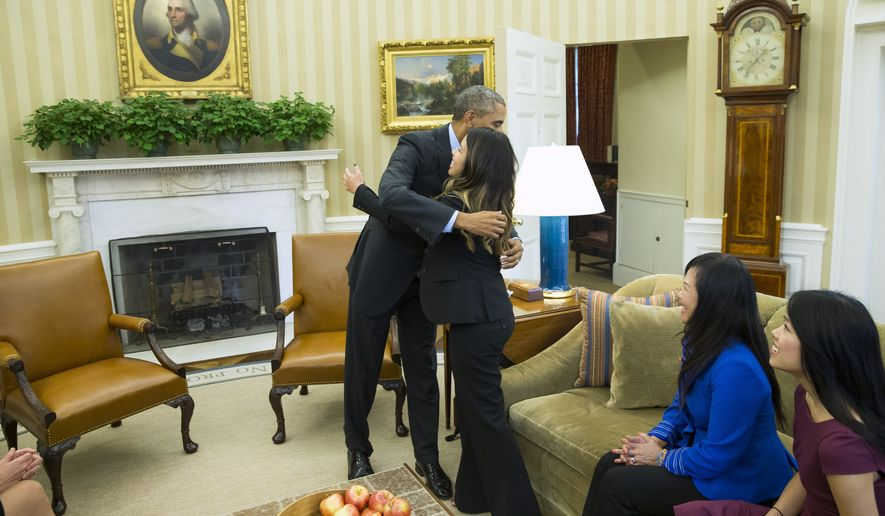 President Barack Obama hugs Ebola survivor Nina Pham in the Oval Office of the White House in Washington, Friday, Oct. 24, 2014. Pham, the first nurse diagnosed with Ebola after treating an infected man at a Dallas hospital is free of the virus. The 26-year-old Pham arrived last week at the NIH Clinical Center. She had been flown there from Texas Health Presbyterian Hospital Dallas. (AP Photo/Evan Vucci)