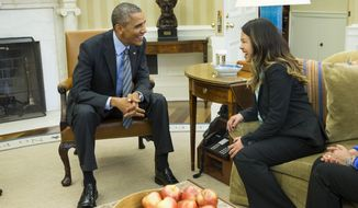 President Barack Obama meets with Ebola survivor Nina Pham in the Oval Office of the White House in Washington, Friday, Oct. 24, 2014. Pham, the first nurse diagnosed with Ebola after treating an infected man at a Dallas hospital is free of the virus. The 26-year-old Pham arrived last week at the NIH Clinical Center. She had been flown there from Texas Health Presbyterian Hospital Dallas. (AP Photo/Evan Vucci)