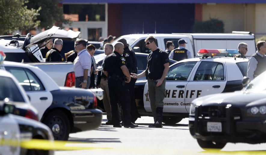 Law enforcement officers gather at the site where a Sacramento County Sheriff's deputy was shot by an assailant who then carjacked two vehicles prompting a manhunt in Sacramento, Calif., Friday, Oct. 24, 2014.  The deputy was taken to a hospital but his condition is not immediately known.(AP Photo/Rich Pedroncelli)