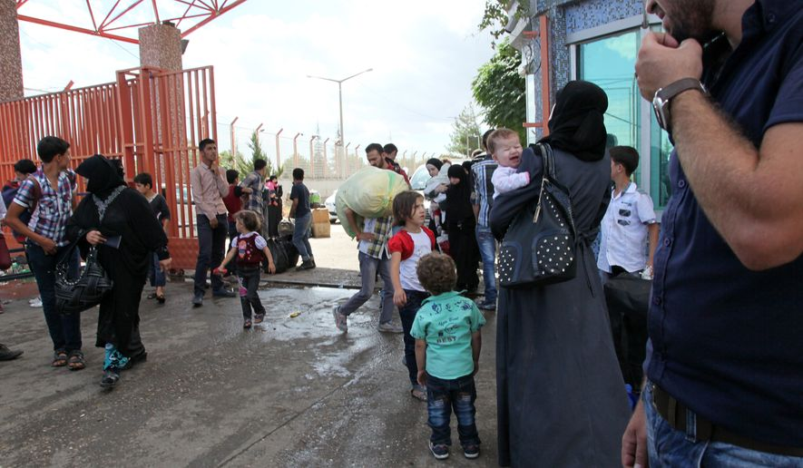 Syrians and Turks are seen at the Turkish border crossing of Oncunipar, Kilis, Turkey, in this Sept. 28, 2014, file photo. (AP Photo/Burhan Ozbilici, File)