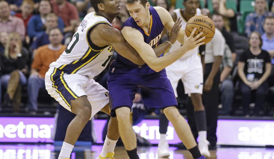 Utah Jazz's Alec Burks, left, defends Phoenix Suns' Goran Dragic, right, during the fourth quarter of an NBA preseason basketball game Friday, Oct. 24, 2014, in Salt Lake City. The Suns won 105-100. (AP Photo/Rick Bowmer)