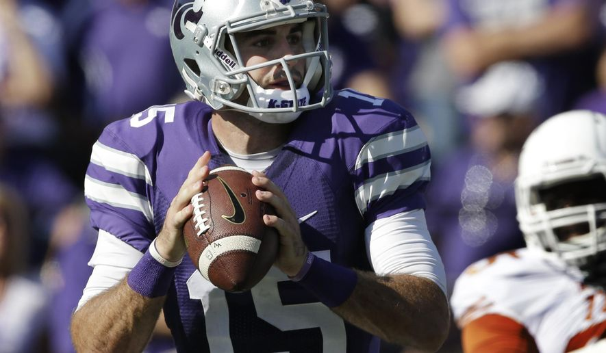 Kansas State quarterback Jake Waters (15) looks for a receiver during the first half of an NCAA college football game against Texas in Manhattan, Kan., Saturday, Oct. 25, 2014. (AP Photo/Orlin Wagner)