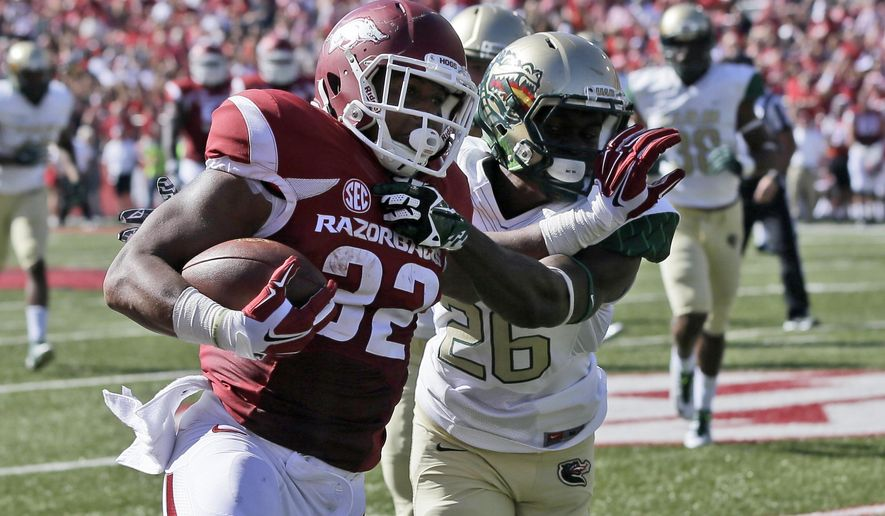 Arkansas running back Jonathan Williams (32) pushes away UAB cornerback Rolan Milligan (26) in the second quarter of an NCAA college football game in Fayetteville, Ark., Saturday, Oct. 25, 2014. (AP Photo/Danny Johnston)