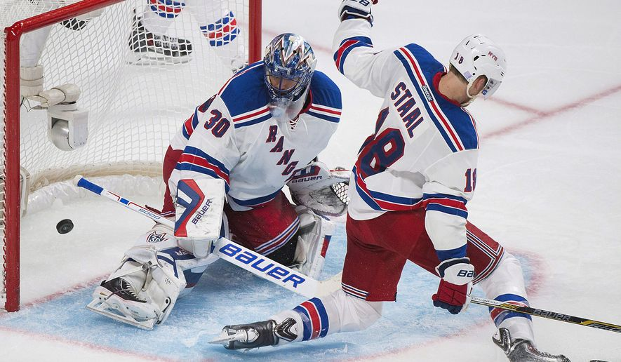 New York Rangers goaltender Henrik Lundqvist (30) is scored on by Montreal Canadiens' Max Pacioretty, not seen, as Rangers' Marc Staal (18) defends during the third period of an NHL hockey game Saturday, Oct. 25, 2014, in Montreal. (AP Photo/The Canadian Press, Graham Hughes)