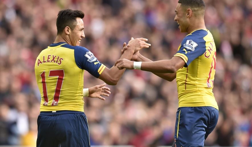 Arsenal's Alexis Sanchez, left, celebrates scoring his side's first goal of the game with teammate Alex Oxlade-Chamberlain during their English Premier League soccer match against Sunderland at the Stadium of Light, Sunderland, England, Saturday, Oct. 25, 2014. (AP Photo/Owen Humphreys, PA Wire)  UNITED KINGDOM OUT     -    NO SALES     -    NO ARCHIVES