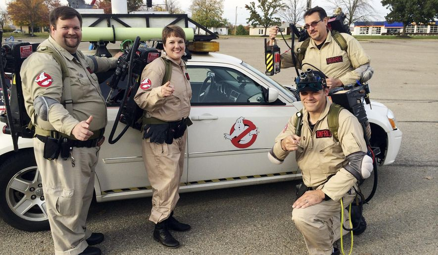 "In this Oct. 20, 2014 photo, member of the Columbus Ghostbusters (from left):  Jamie Knapp, Theresa Knapp, Brian Onofrio and Jeff Tatarek  pose by their ""Ekto Magnum"" car in Columbus, Ohio. The group, impersonating characters from the 1984 movie, is one of several active in the state. (AP Photo/Columbus Dispatch, Kevin Joy)"