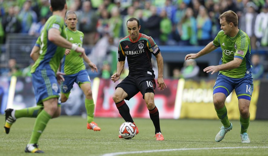 Los Angeles Galaxy midfielder Landon Donovan, center, dribbles the ball as Seattle Sounders' Chad Marshall, right, closes in during the first half of an MLS soccer match, Saturday, Oct. 25, 2014, in Seattle. (AP Photo/Ted S. Warren)