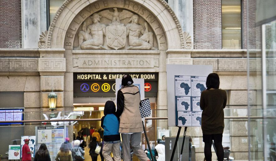 Health alerts regarding people who may have traveled to particular West African countries are posted the main lobby entrance of Bellevue Hospital, Friday Oct. 24, 2014 in New York.   Dr. Craig Spencer, a resident of New York City and a member of Doctors Without Borders, was admitted to Bellevue Thursday and has been diagnosed with Ebola.  (AP Photo/Bebeto Matthews)
