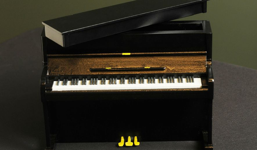In this Oct. 23, 2014 photo, a composite ceramic custom printed 3-D funeral urn depicting a piano, made by Foreverence, is seen in Eden Prairie, Minn. Foreverence sells the urns via funeral directors, The St. Paul Pioneer Press reported. (AP Photo/The St. Paul Pioneer Press, Scott Takushi)