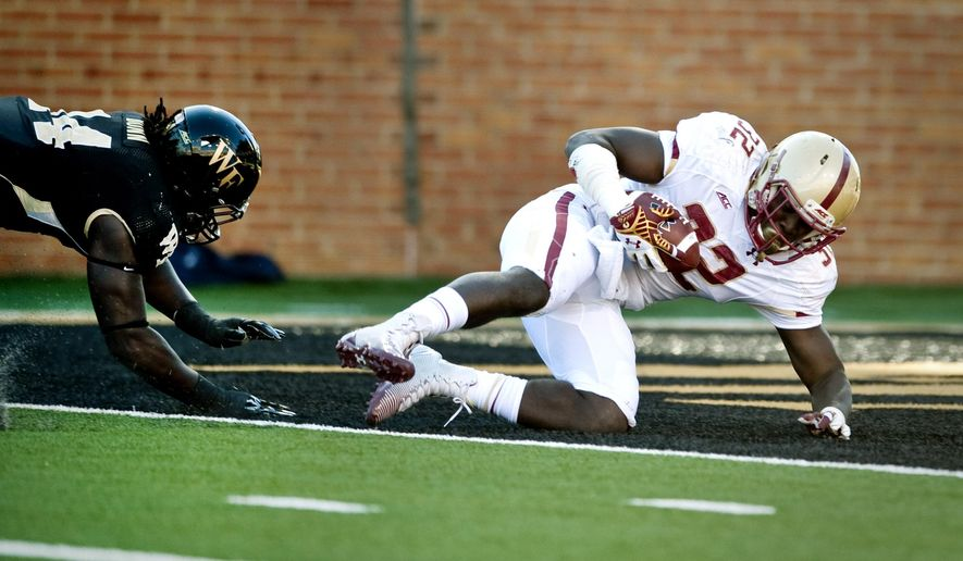 Boston College running back Jon Hilliman, right, scores a touchdown as Wake Forest defensive end Wendell Dunn, left, defends during the first half of an NCAA college football game in Winston-Salem, N.C. Saturday, Oct. 25, 2014. (AP Photo/Winston-Salem Journal, Lauren Carroll)
