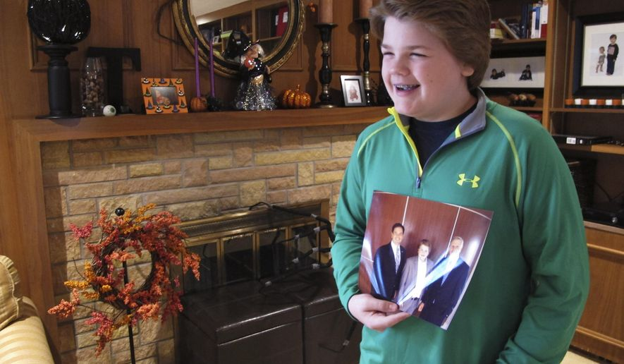 In this Oct. 17, 2014 photo, Jed Thomas, an eighth-grader from Fargo, N.D., holds up a photograph of his meeting with Jeb Bush and talks about his possible political career. He says he would like to start his own version of the Tea Party someday. (AP Photo/Dave Kolpack)