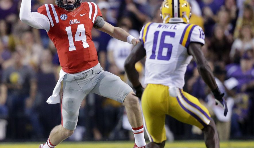 Mississippi quarterback Bo Wallace (14) pump-fakes as he carries against LSU defensive back Tre'Davious White (16) during the first half of an NCAA college football game in Baton Rouge, La., Saturday, Oct. 25, 2014. (AP Photo/Gerald Herbert)