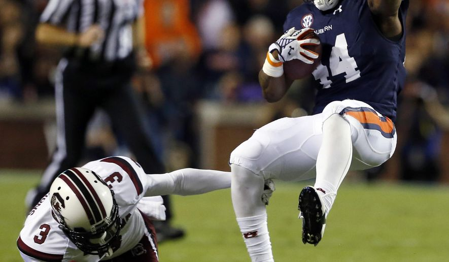 Auburn running back Cameron Artis-Payne (44) spins around out of the tackle of South Carolina cornerback Chris Lammons (3) during the first half of an NCAA college football game Saturday, Oct. 25, 2014, in Auburn, Ala. (AP Photo/Butch Dill)