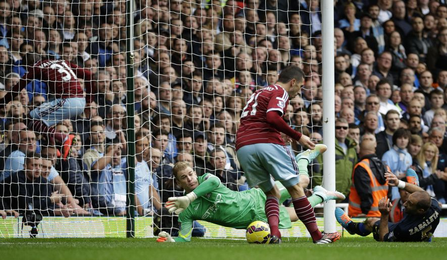West Ham's Morgan Amalfitano, center, scores past Manchester City's goalkeeper Joe Hart as West Ham United's Enner Valencia, left, jumps in the crowd from his momentum from running down the pitch during the English Premier League soccer match between West Ham and Manchester City at Upton Park stadium in London, Saturday, Oct. 25, 2014. (AP Photo/Matt Dunham)