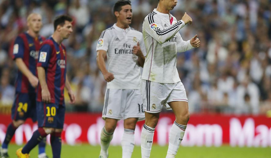Real Madrid's Cristiano Ronaldo, right, gestures next to Barcelona's Lionel Messi, second left, during a Spanish La Liga soccer match between Real Madrid and FC Barcelona at the Santiago Bernabeu stadium in Madrid, Spain, Saturday, Oct. 25, 2014. (AP Photo/Andres Kudacki)