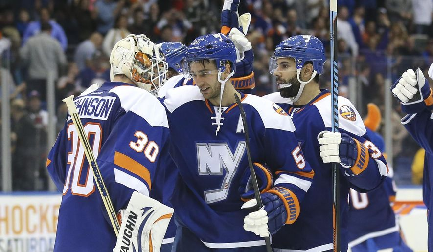 New York Islanders center Frans Nielsen (51) celebrates with goalie Chad Johnson (30) after scoring a hat trick and winning their NHL hockey game against the Dallas Stars, Saturday, Oct. 25, 2014, in Uniondale, N.Y. The Islanders won, 7-5. (AP Photo/John Minchillo)