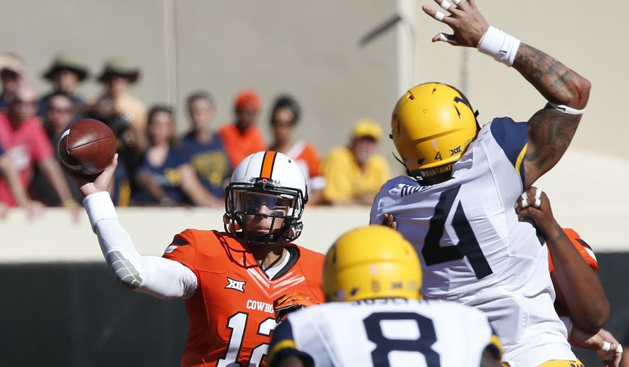 Oklahoma State quarterback Daxx Garman (12) passes under pressure from West Virginia defensive lineman Shaquille Riddick (4) and safety Karl Joseph (8) in the first half of an NCAA college football game in Stillwater, Okla., Saturday, Oct. 25, 2014. (AP Photo/Sue Ogrocki)