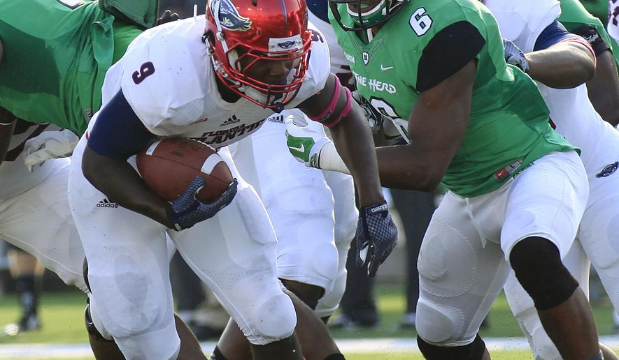 Florida Atlantic's Greg Howell, left, gets by Marshall's Neville Hewitt on Saturday, Oct. 25, 2014 during an NCAA college football game in Huntington, W.Va. Marshall won 35-16. (AP Photo/Randy Snyder)