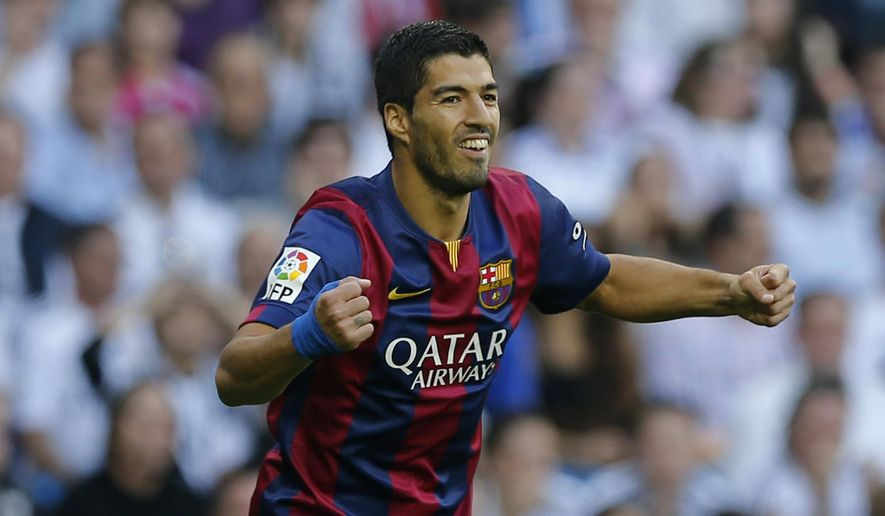 CORRECTING PLAYER WHO SCORED TO NEYMAR - Barcelona's Luis Suarez celebrates after Barcelona teammate Neymar scored during a Spanish La Liga soccer match between Real Madrid and Barcelona at the Santiago Bernabeu stadium in Madrid, Spain, Saturday Oct. 25, 2014. (AP Photo/Paul White)