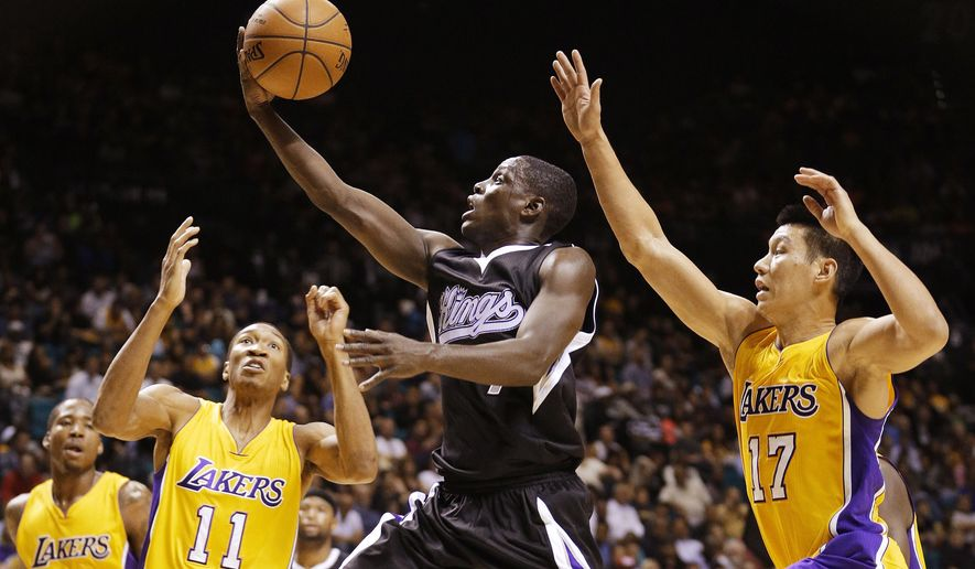 Sacramento Kings guard Darren Collison, center, goes up for a shot against Los Angeles Lakers forward Wesley Johnson, left, and guard Jeremy Lin, right, during an NBA preseason basketball game Friday, Oct. 24, 2014, in Las Vegas. The Kings won 93-92. (AP Photo/John Locher)