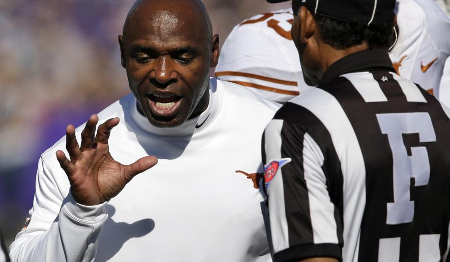 Texas head coach Charlie Strong, left, has words with field judge Nick Lave during the first half of an NCAA college football game against Kansas State in Manhattan, Kan., Saturday, Oct. 25, 2014. (AP Photo/Orlin Wagner)