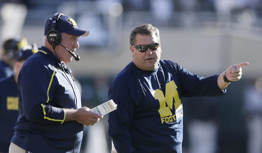 Michigan head coach Brady Hoke, right, talks with defensive coordinator Greg Mattison during the first half of an NCAA college football game against Michigan State in East Lansing, Mich., Saturday, Oct. 25, 2014. (AP Photo/Carlos Osorio)