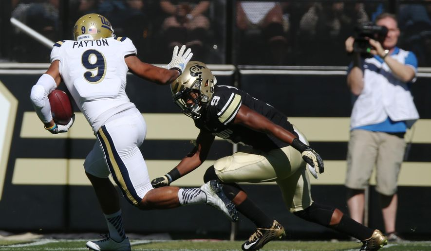 UCLA wide receivr Jordan Payton, left, heads in for touchdown after catching pass in front of Colorado defensive back Tedric Thompson in the first quarter of an NCAA football game in Boulder, Colo., on Saturday, Oct. 25, 2014. (AP Photo/David Zalubowski)