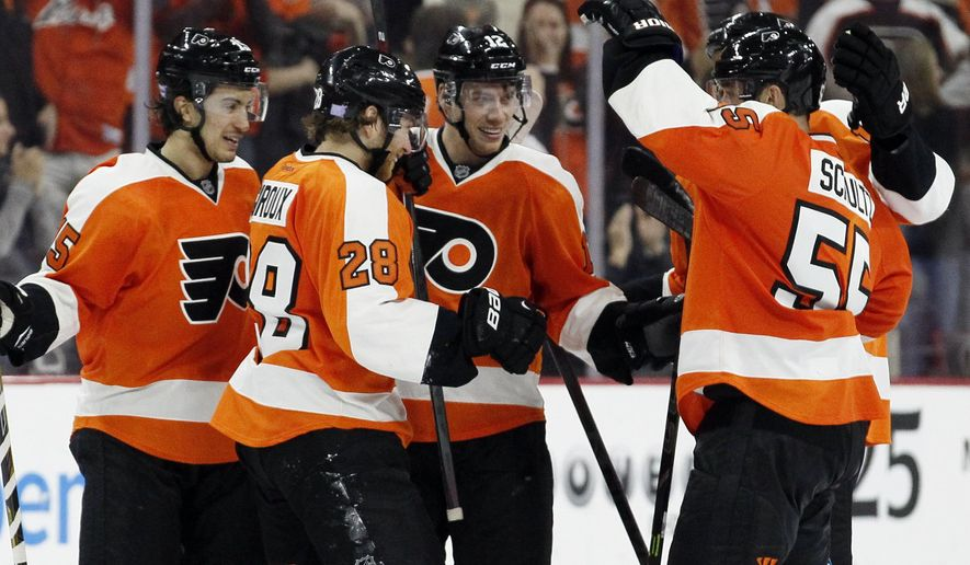 Philadelphia Flyers' Michael Raffl (12), center, celebrates his empty-net goal with teammates in the closing minute of the third period of an NHL hockey game against the Detroit Red Wings, Saturday, Oct. 25, 2014, in Philadelphia. The Flyers won 4-2. (AP Photo/Tom Mihalek)