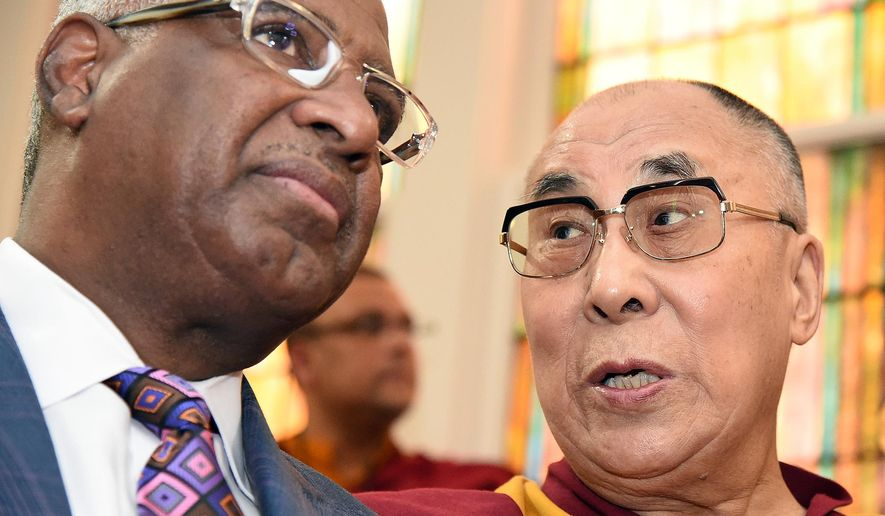 The Dalai Lama visits the Sixteenth Street Baptist Church in Birmingham, Ala., Saturday, Oct. 25, 2014,  as protesters and supporters chanted outside. Birmingham Mayor William Bell sat with Dalai Lama and they held hands most of the time. (AP Photo/AL.com, Joe Songer)