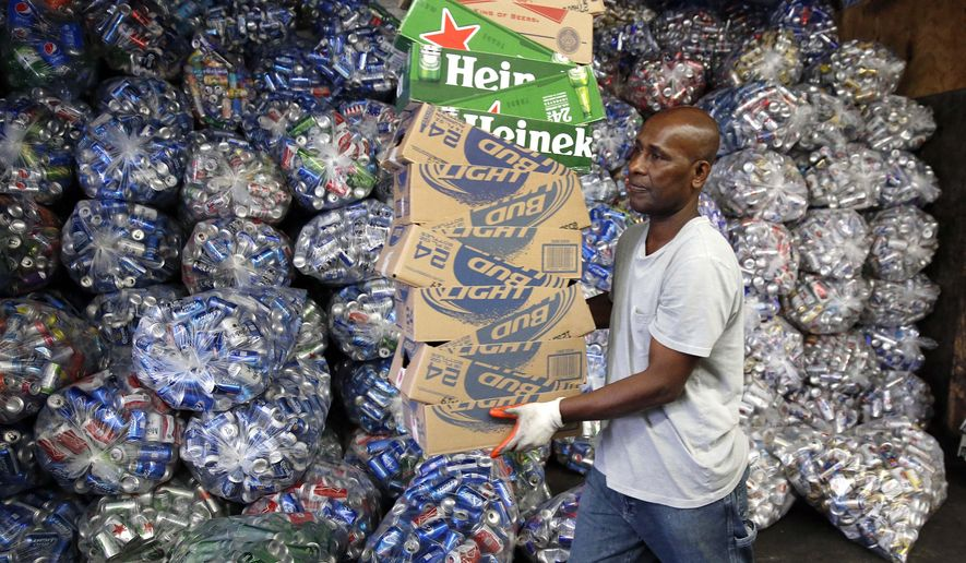 In this Tuesday, Sept. 30, 2014 photo, Jorge Pereira works at sorting bottles and cans at a redemption center in the East Boston neighborhood of Boston. If approved on Nov. 4, a ballot measure would expand the state's law by adding 5-cent deposits to most non-alcoholic and non-carbonated beverage containers. (AP Photo/Michael Dwyer)