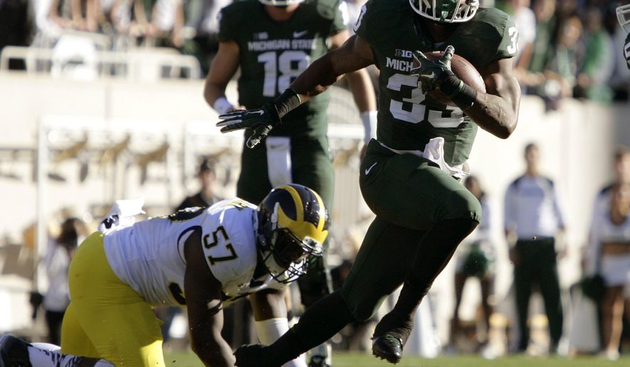 Michigan State's Jeremy Langford (33) rushes past Michigan's Frank Clark (57) as Michigan State quarterback Connor Cook (18) watches during the first quarter of an NCAA college football game, Saturday, Oct. 25, 2014, in East Lansing, Mich. (AP Photo/Al Goldis)