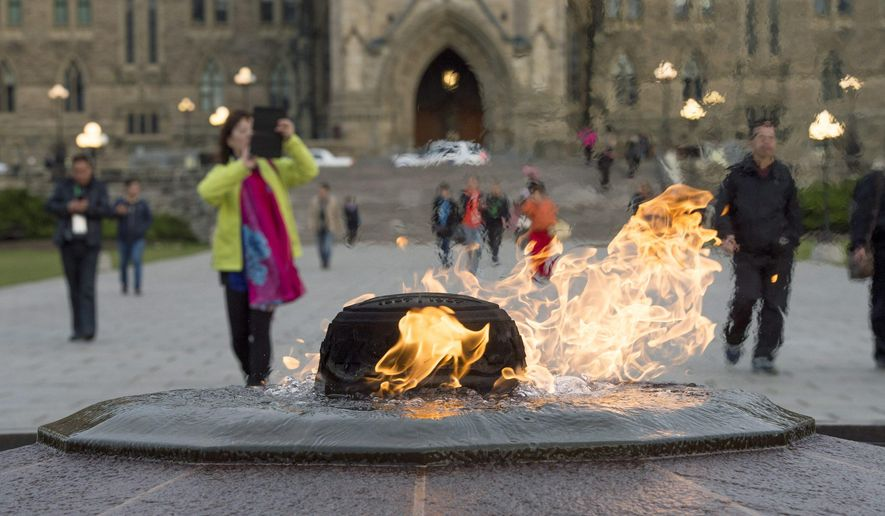 Visitors walk past the Centennial Flame on Parliament Hill in Ottawa, Ontario, Saturday, Oct. 25, 2014. The grounds and lawn of Parliament Hill reopened Friday night following the shootings at the National War Memorial and Parliament Hill. (AP Photo/The Canadian Press, Justin Tang)